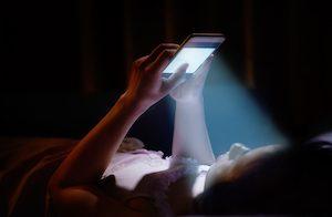 Blaulicht strahlt vom Handy in die Augen