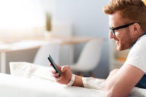 Mann trägt Blaulichtfilterbrille und surft am Handy