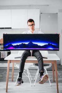 Mann mit Brille hält einen großen Bildschrim