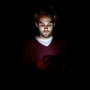 Mann mit Smartphone bei Nacht und Blaulichtfilter